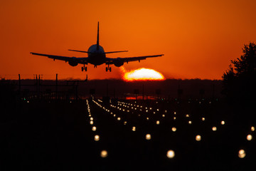 Tuinposter Silhouette of air plane landing on illuminated track at sunset with beautiful red sky and sun in background