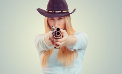 Cowgirl aiming at camera with gun