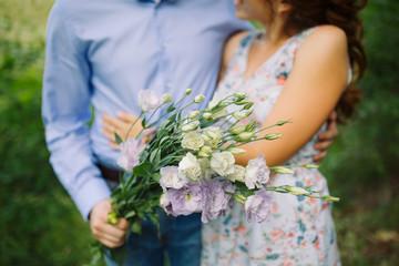 white eustoma flowers in hands of guy who hugs girl