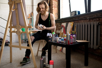 Full length portrait of handsome long haired artist painting on easel while enjoying  work in art studio, copy space