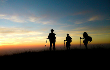 silhouette of hikers in sunset