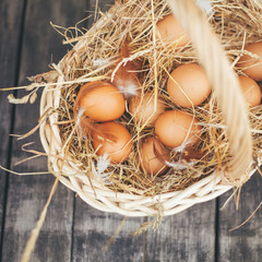 Chicken eggs lie in a wicker basket with hay