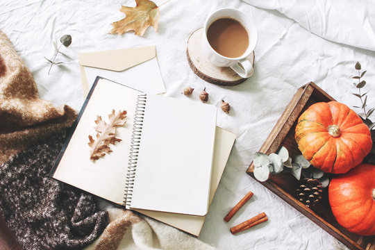 Autumn breakfast in bed composition. Card, notebook mockup. Cup of coffee, eucalyptus leaves, pumpkins on wooden tray. White linen background. Thanksgiving, halloween concept. Flat lay, top view.