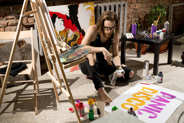 Full length high angle portrait of contemporary male artist painting banner  while sitting on floor in art studio, copy space