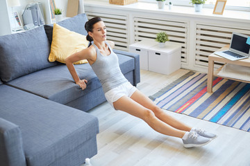 Fit young sportswoman doing physical exercises by sofa in living-room at leisure Fototapete
