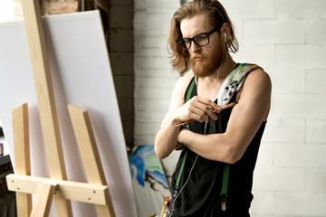 Waist up portrait of contemporary long haired artist looking at picture standing by easel in art studio, copy space