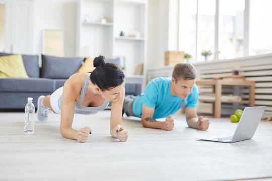 Contemporary young active couple in sportswear doing planks on the floor in front of laptop while watching online workout