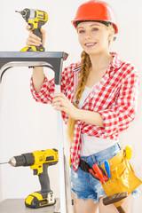 Woman wearing helmet using drill