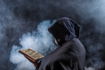 a mysterious figure holds a book in his hands Wall mural