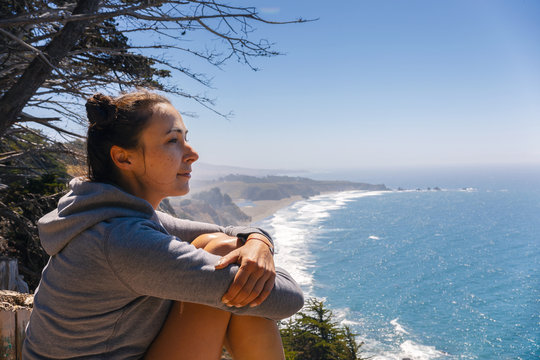 Woman sitting at edge of cliffs