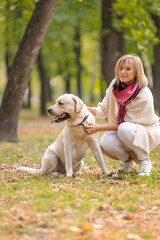 Beautiful young woman walks with her retriever in the park in autumn.