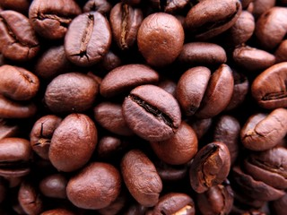 Macro close up of dense bunch of aromatic roasted brown coffee beans in variety of brown shades