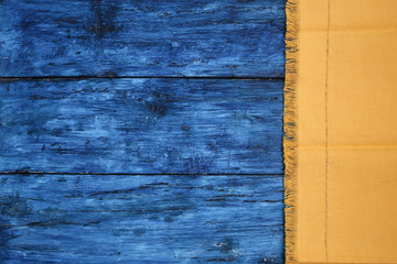 Yellow napkin from right side of dark blue painted board