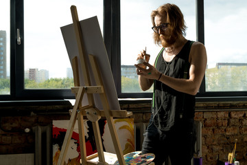 Portrait of contemporary male artist painting pictures standing by easel in art studio lit by sunlight, copy space