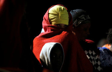 Migrants wait to disembark a rescue boat after arriving at the port of Malaga