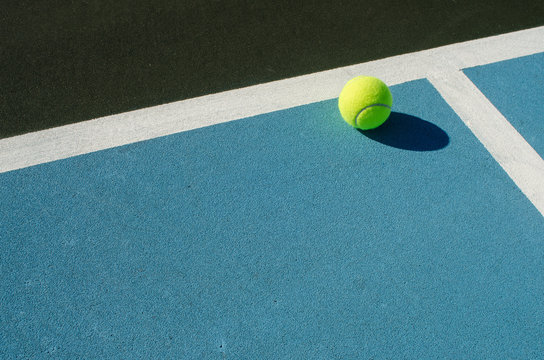 Tennis ball rests on blue tennis court
