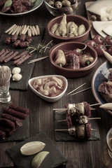 Tapas appetizers on wooden table. Vintage effect