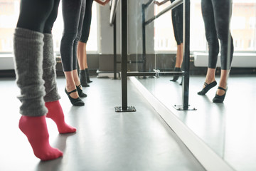 Low section view at row of elegant young women practicing ballet moves standing by bar against mirror in dance studio