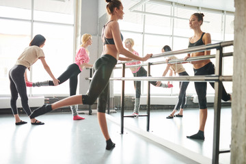 Full length portrait of female ballet teacher positioning students in dance class  at bar before mirror, copy space