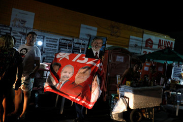 A person holds a flag and a photograph of former Brazilian president Luiz Inacio Lula da Silva, in Fortaleza