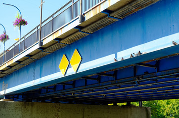 Ailing blue rusty pedestrian bridge over a river in the city with doves and flowers to illustrate poor infrastructure in Germany