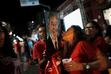 A woman kisses a photograph of former Brazilian president Luiz Inacio Lula da Silva, in Fortaleza