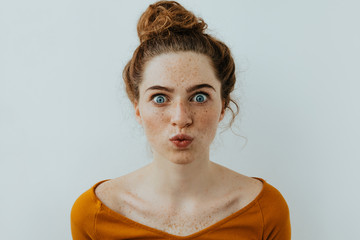 Woman portrait. Style. Beautiful blue eyed girl with freckles is pouting lips at camera, on a white background Wall mural