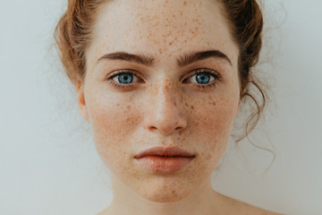 Woman portrait. Close-up. Beautiful blue eyed girl with freckles is looking at camera, on a white background