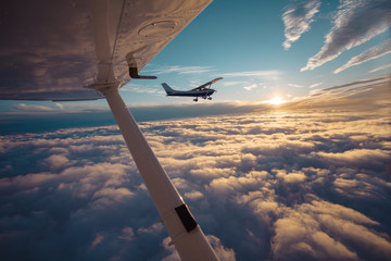Small single engine airplane flying in the gorgeous sunset sky through the sea of clouds Wall mural