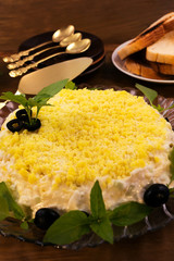 Cold appetizer with yellow top layer, decorated with basil  leaves and black olives.