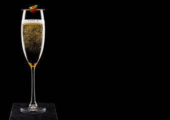 Elegant glass of yellow champagne with rasspbery on stick on black marble board on black background.