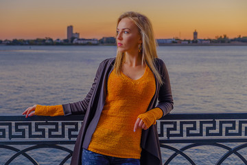 Beautiful 30s blond haired Woman Standing Outdoors Near The River Leaning Back Ornate Fence