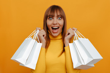 Shopping. Emotion. Woman portrait. Excited girl is holding shopping bags and looking at camera with an open mouth, on a yellow background