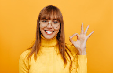 Woman portrait. Emotion. Beautiful young woman in eyeglasses is showing Ok sign, looking at camera and smiling, on a yellow background