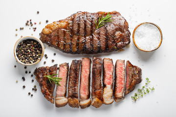 Two grilled marbled beef steaks striploin with spices isolated on white background, top view Wall mural