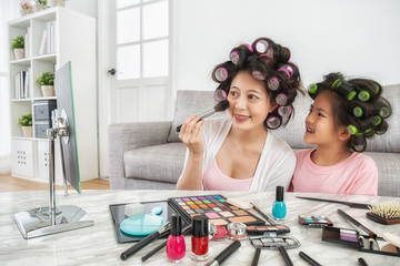 mom doing makeup and her child looking at her