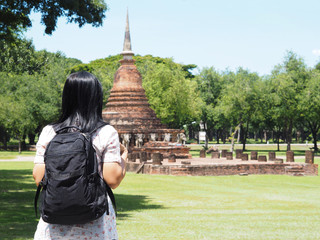 Back view of Asian woman backpacker looking to ruin pagoda at old temple