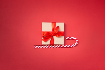 Christmas sledge - a gift box over candy cane on a red background. Abstract christmas concept.