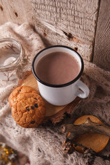 A cup of warm cocoa with traditional american cookies on a brown knitted scarf. Cozy Autumn, fall, winter holiday concept
