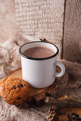 Cup of hot cocoa on rustic wooden bench with knitting soft scarf, closeup photo of warm sweater with american cookies, winter morning concept, front view