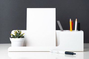 modern office stationery on white table and dark grey wall.pencil, notepad,ruler,pen and pencil box with plant.Mock up paper note for display of design or content.