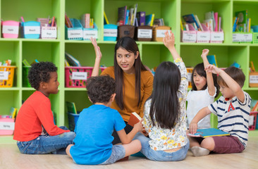 Asian female teacher teaching and asking mixed race kids hand up to answer in classroom,Kindergarten pre school concept.