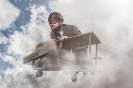 Businessman flying with a wooden toy plane