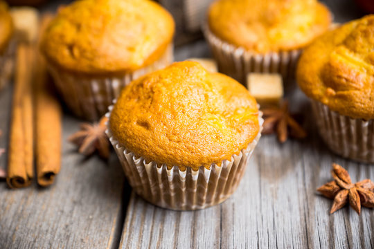 Homemade atutumn muffins with pumpkin, apples and spices on the rustic background. Selective focus.