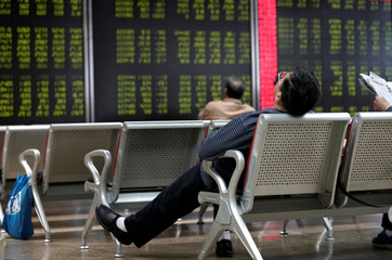 An investor takes a nap in front of a board showing stock information in Beijing