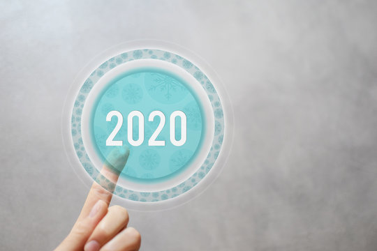 2020 - finger pressing round transparent button with illustrated snowflakes pattern on virtual touchscreen interface to start new year copy space for text. Happy new year concept.