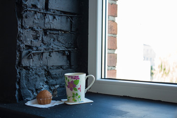 a cup with tea and cupcake near the window