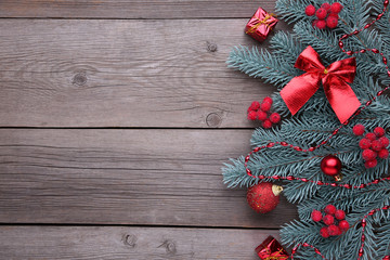 Christmas decoration. Fir-tree branch with balls, bumps, berries of viburnum and gifts on a grey background