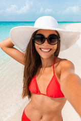 Happy girl taking selfie in summer beach vacation smiling of fun on tropical Caribbean holidays. Asian woman holding camera phone taking picture outside.