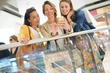 Girls in shopping mall using smartphone